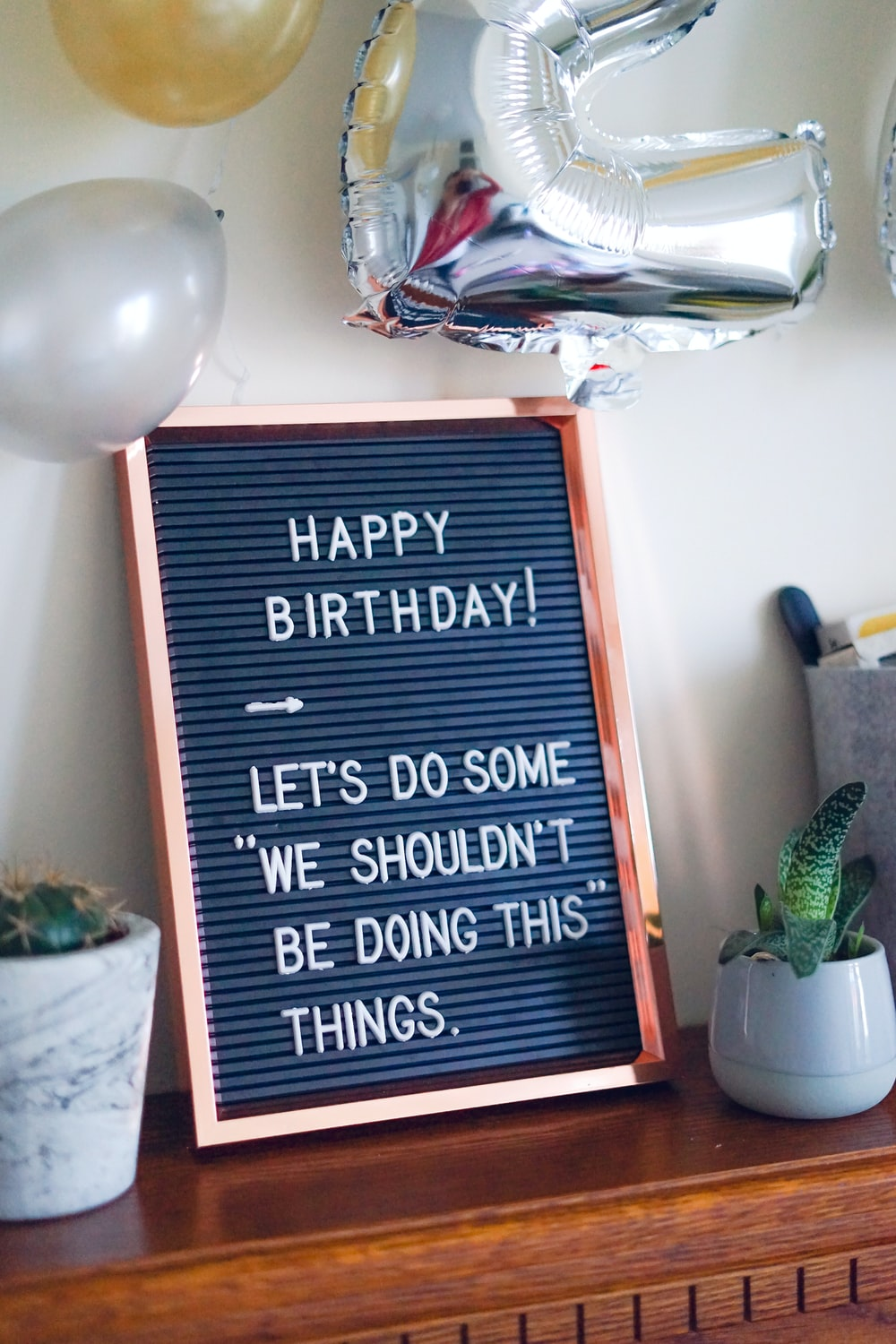 gray and black birthday quote-printed decor beside green snake plant