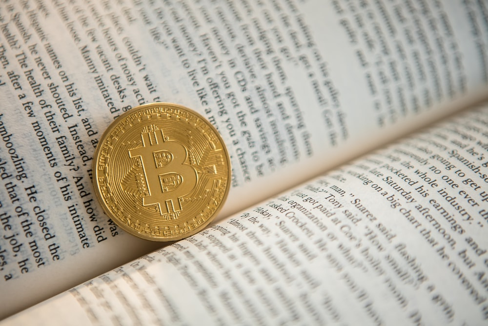 gold-colored Bitcoin on book