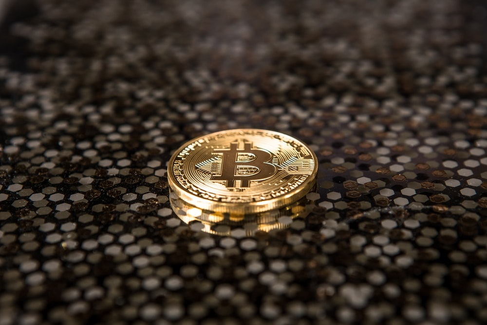 gold-colored Bitcoin coin on ground