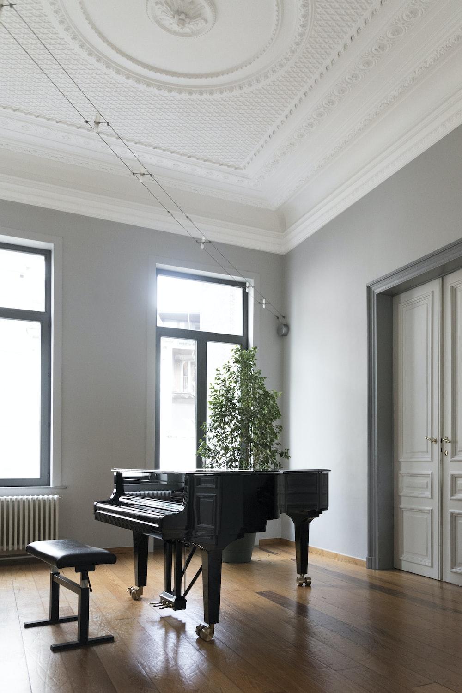 brown grand piano inside white room