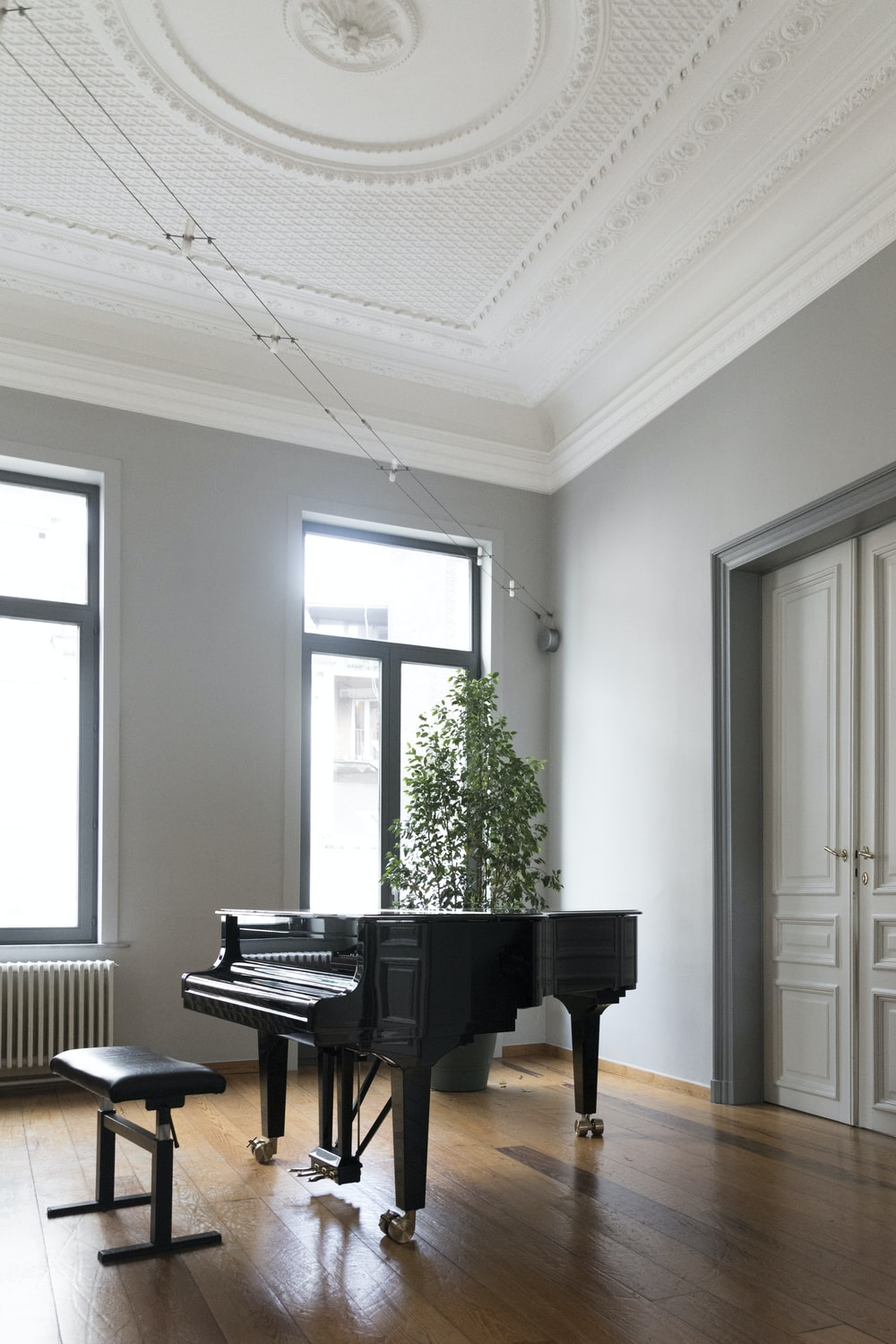 brown grand piano inside white room