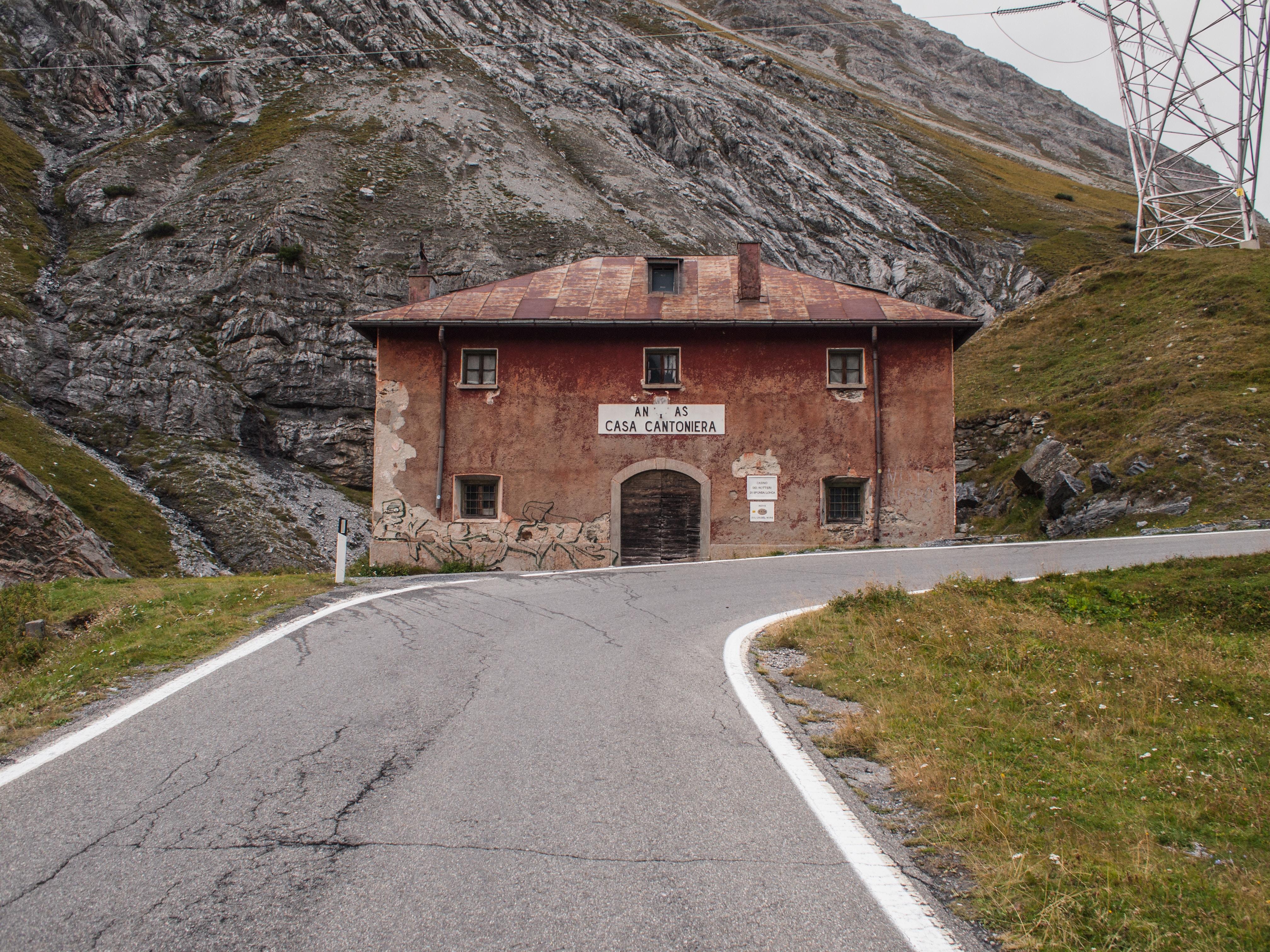 brown brick building beside curved blacktop road