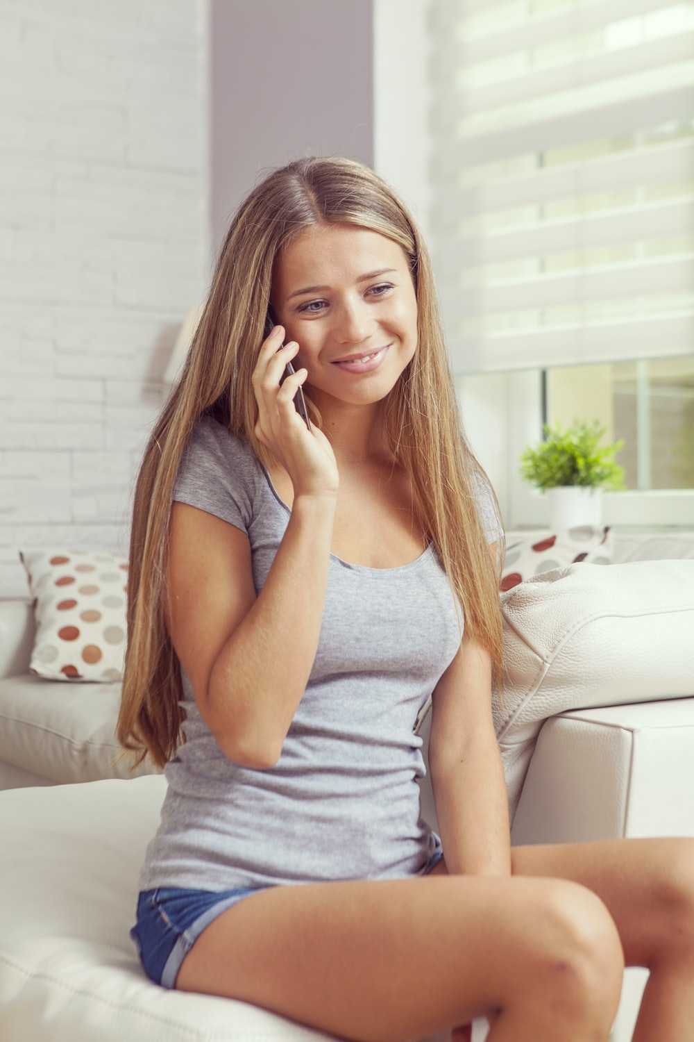 woman sitting on sofa while holding smartphone