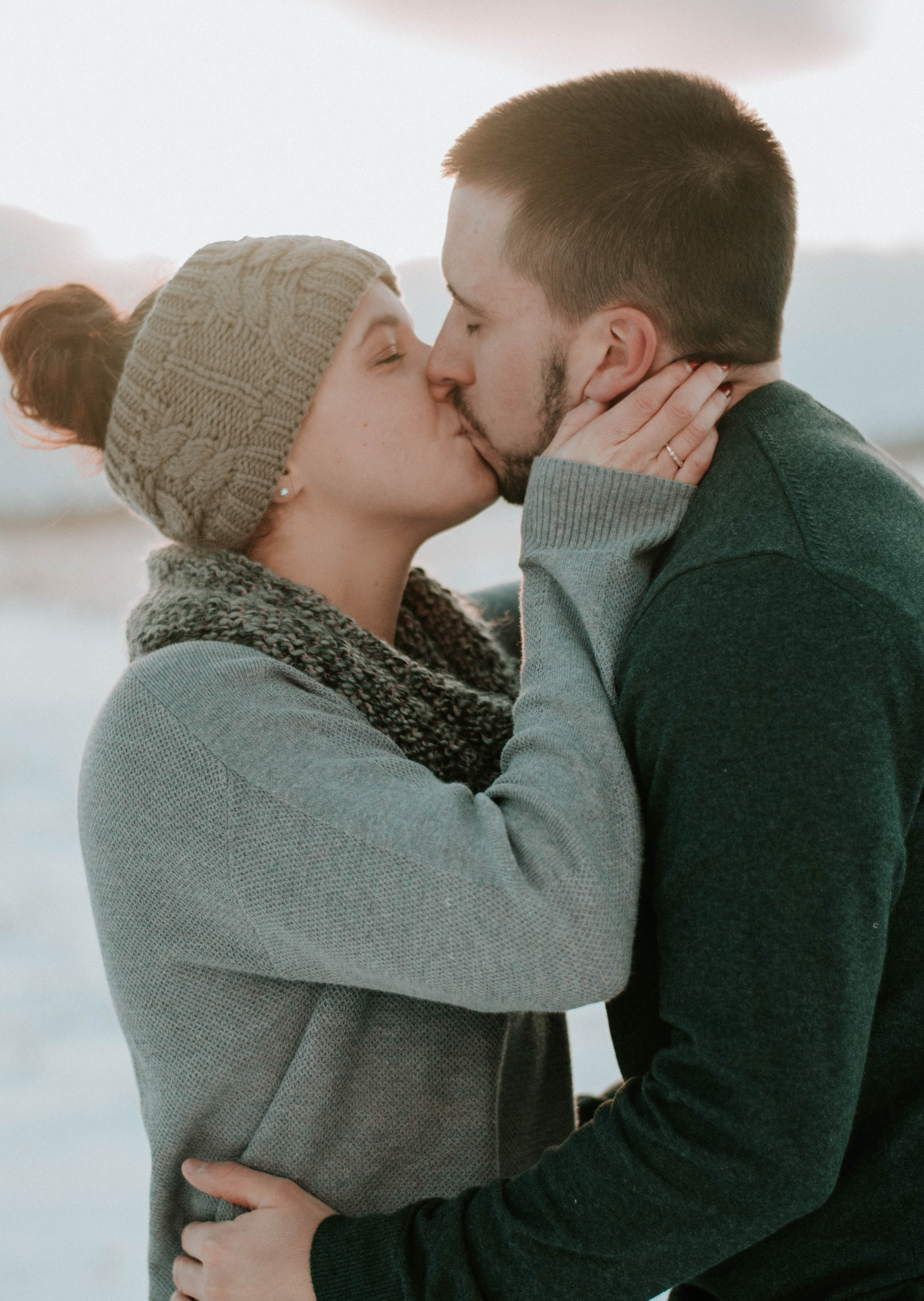 man and woman kissing under white sky at daytime