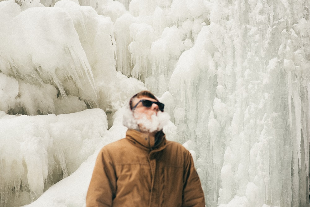 man smoking near ice wall