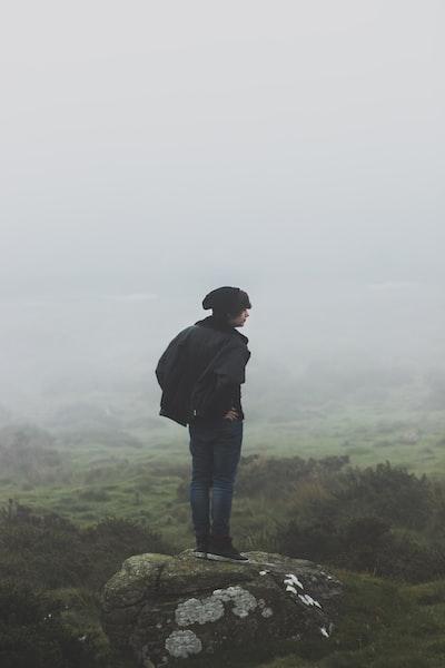 man wearing black jacket standing on rock