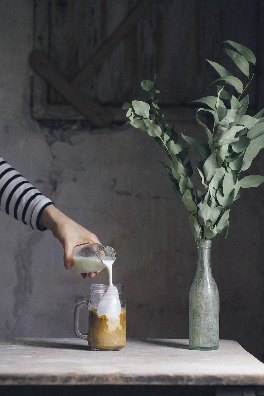person pouring milk on glass mason jar