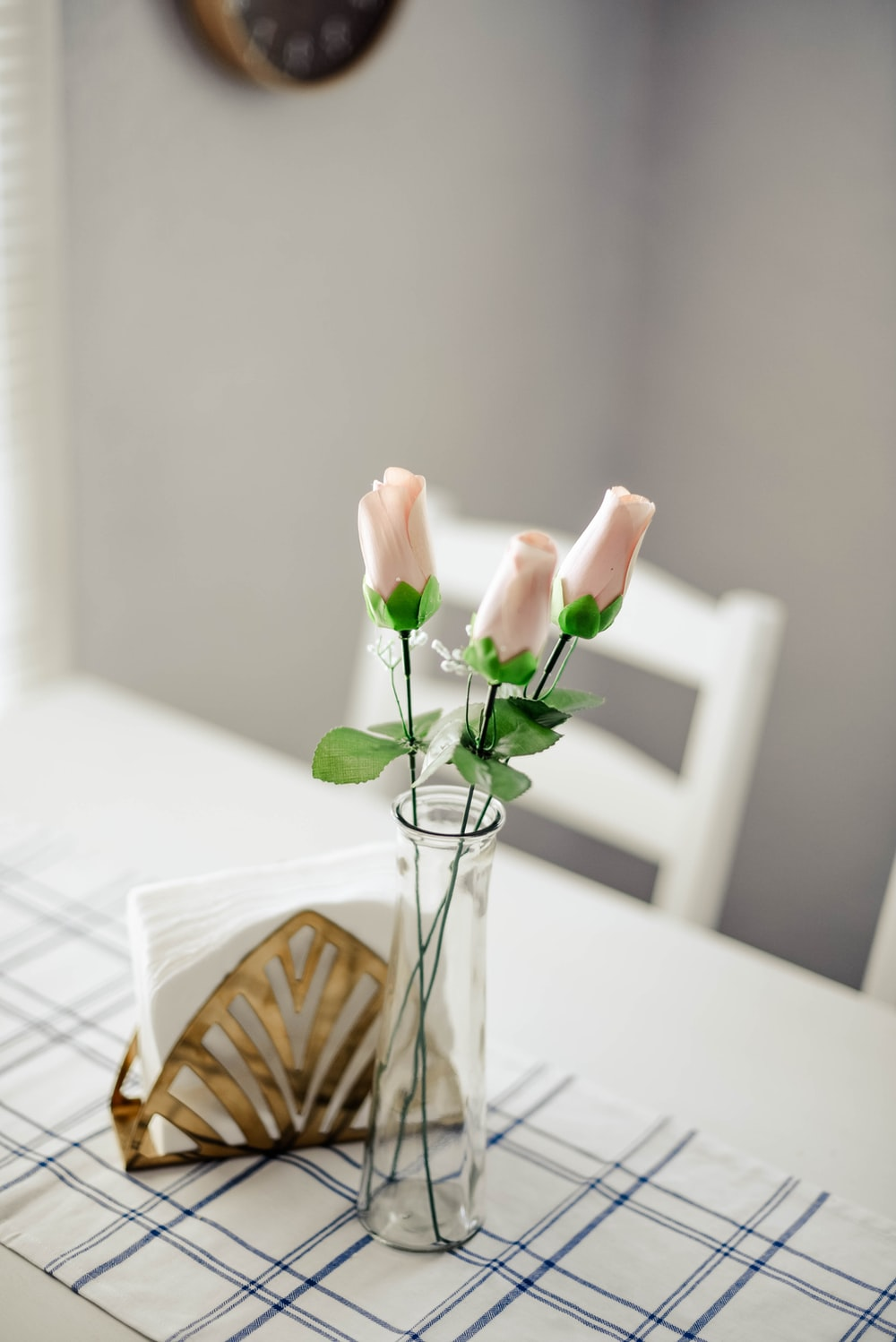 three pink flowers in clear glass vase