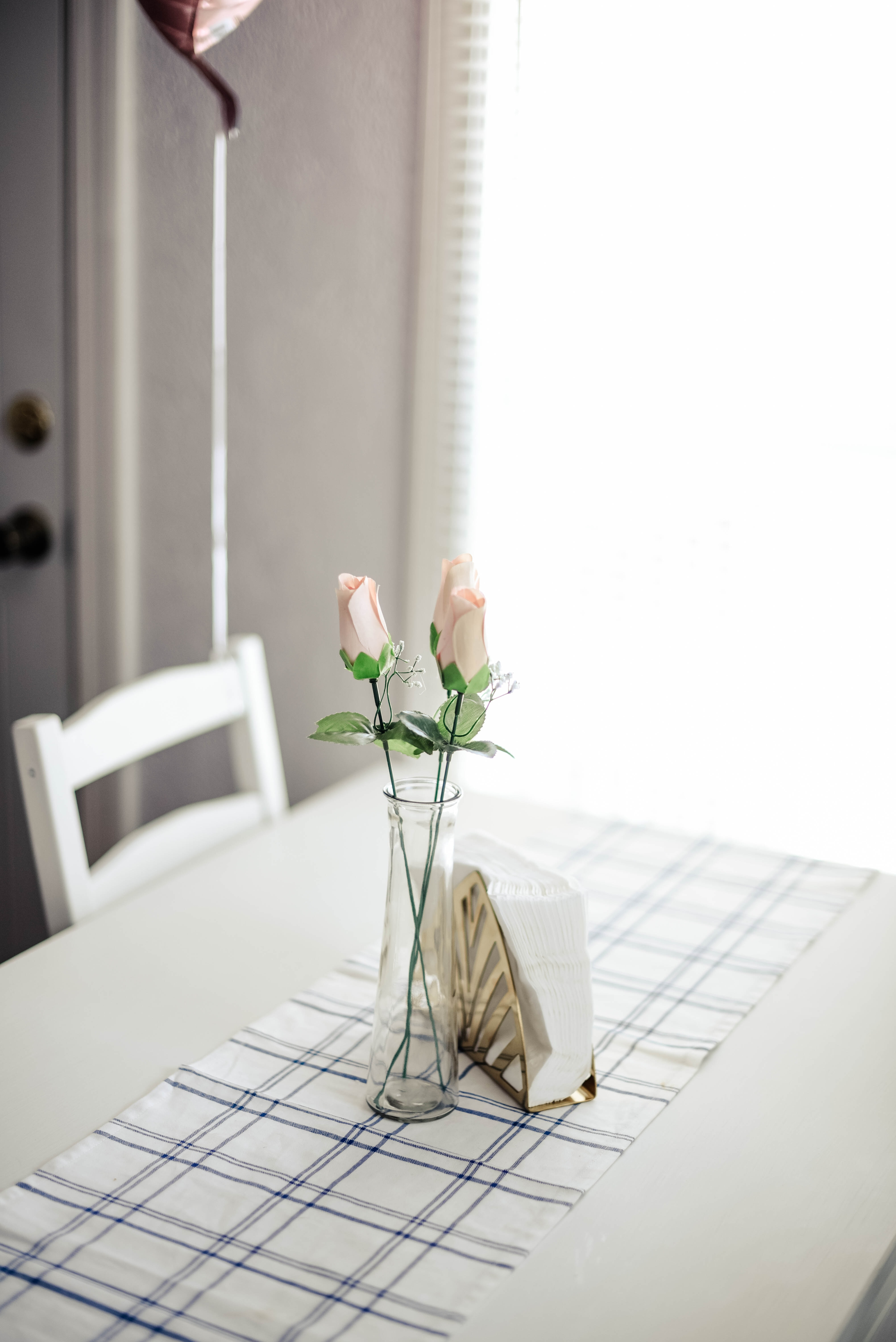 pink roses in glass vase in dining table