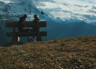 two person sitting on bench under white and blue clouds