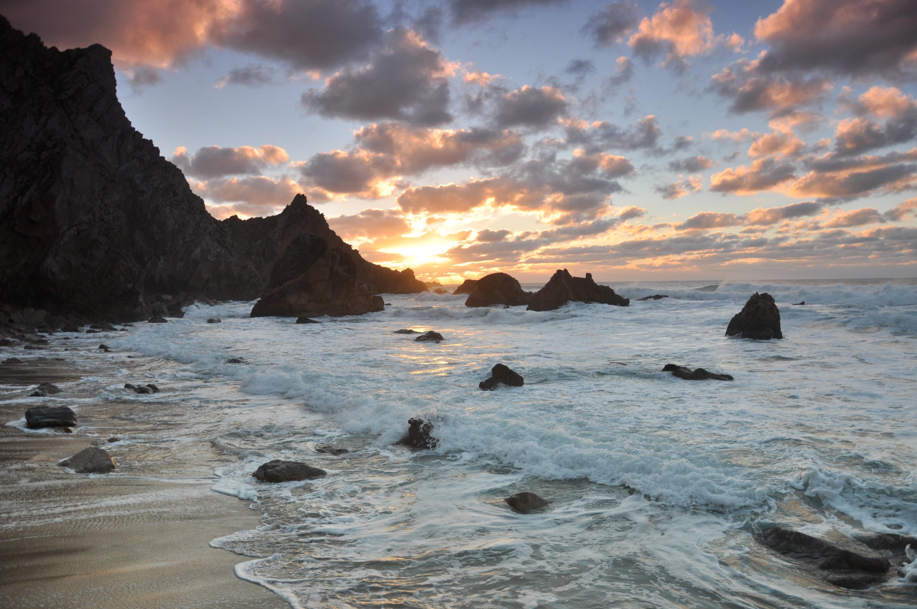 photo of seashore near rocks