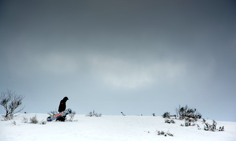 man carrying snowboard in snow field