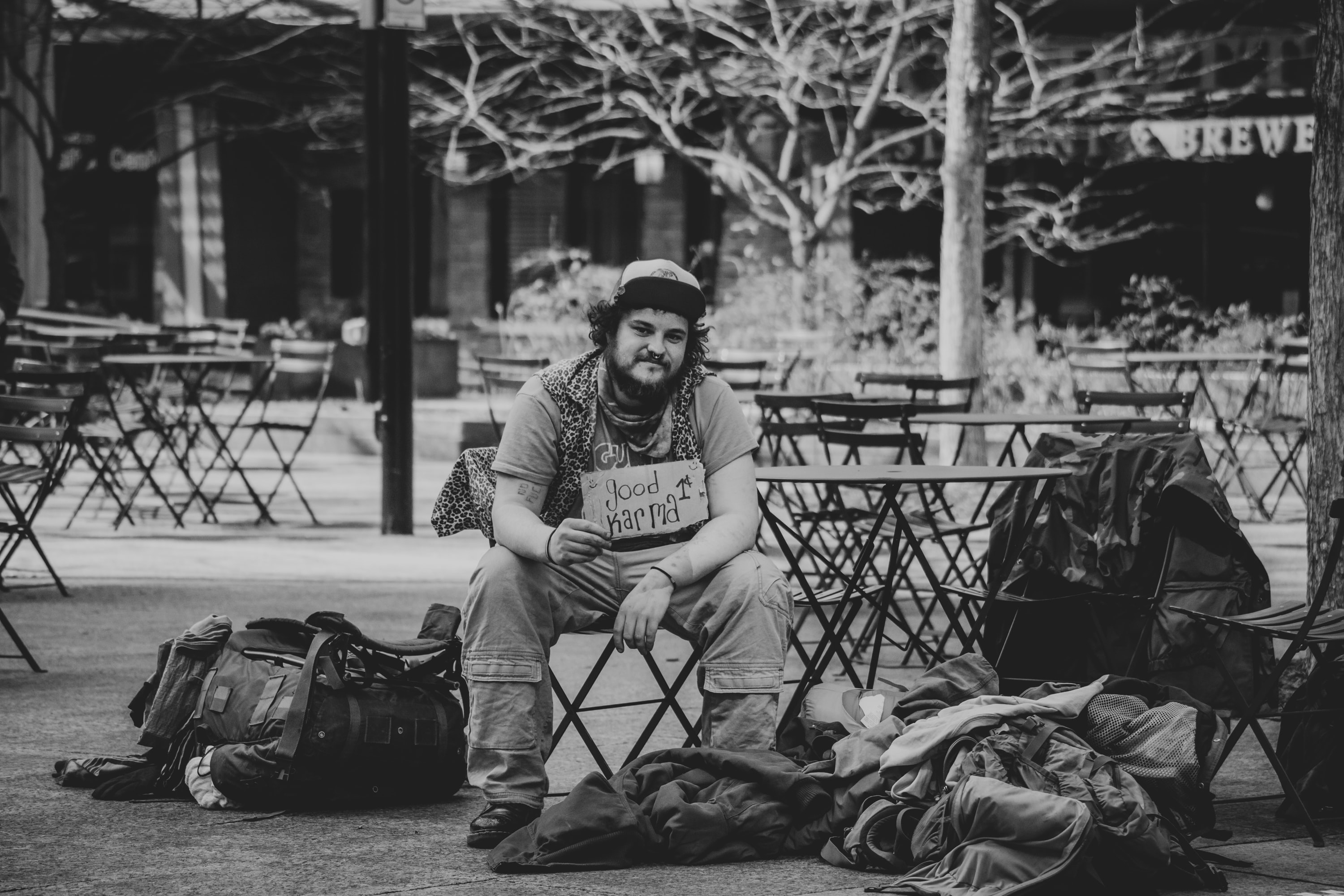 man smiling sitting on bench grayscale photography