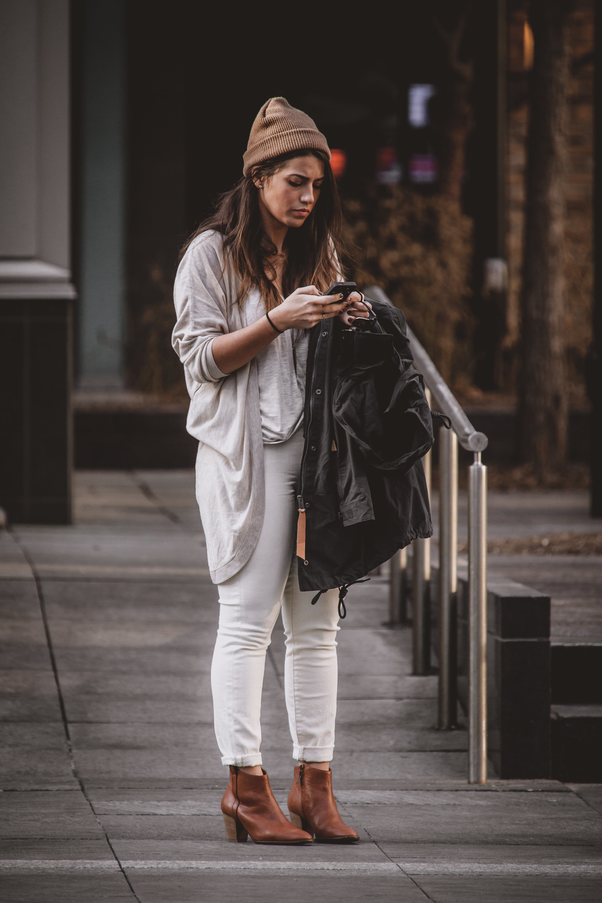 photography of woman in gray cardigan using her mobile phone