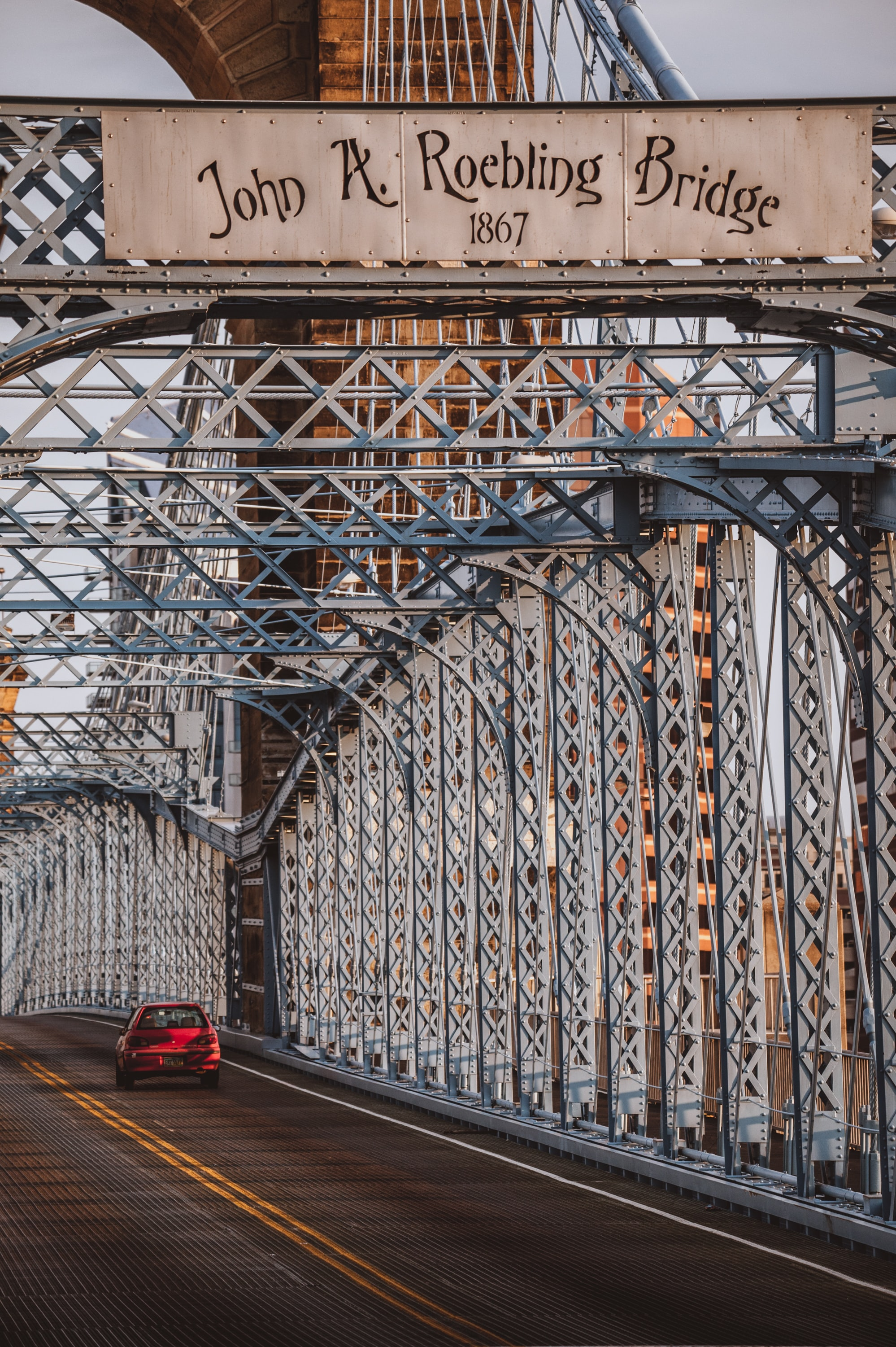 red 5-door hatchback driving on John A. Roebling Bridge