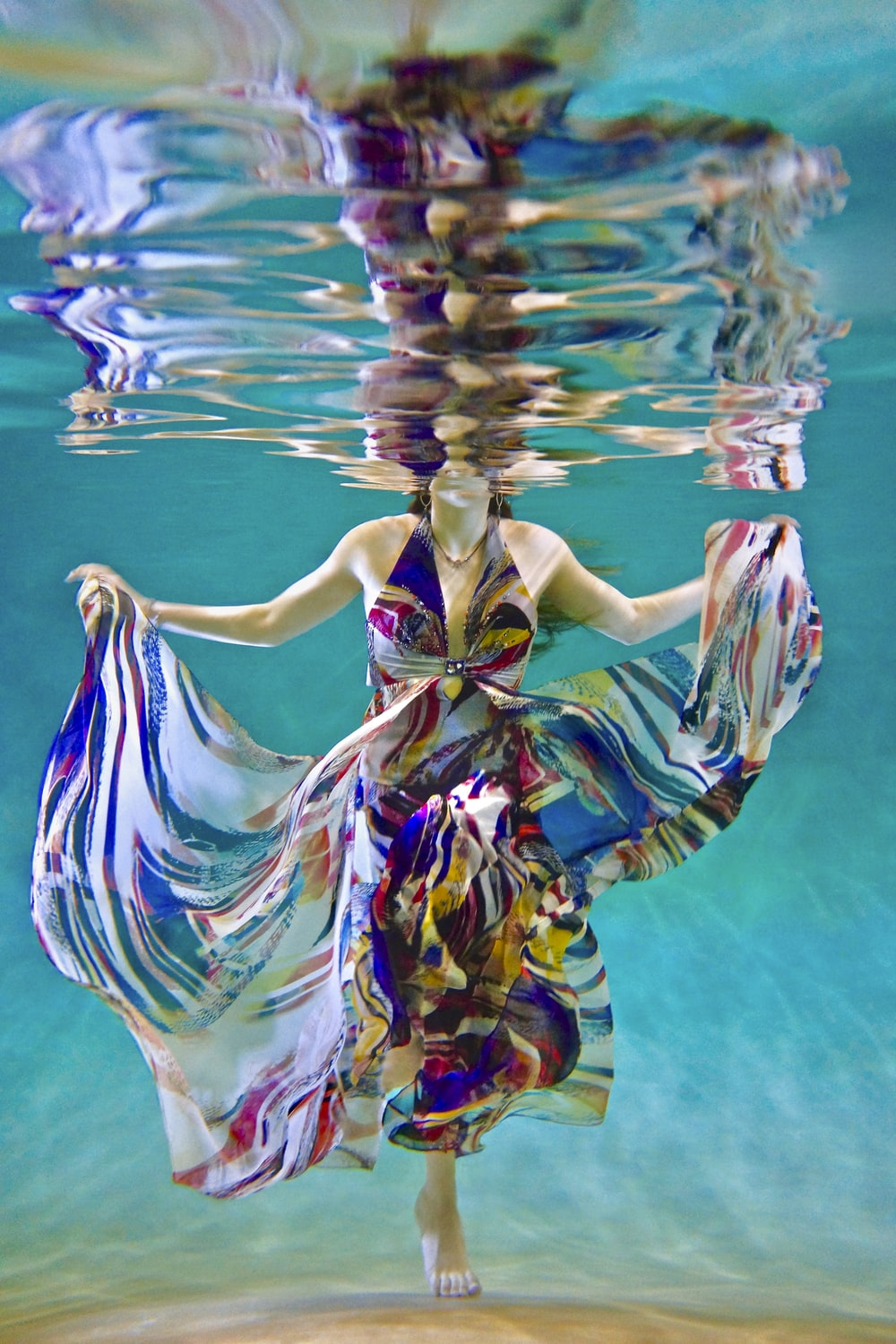 underwater photography of woman in dress swimming