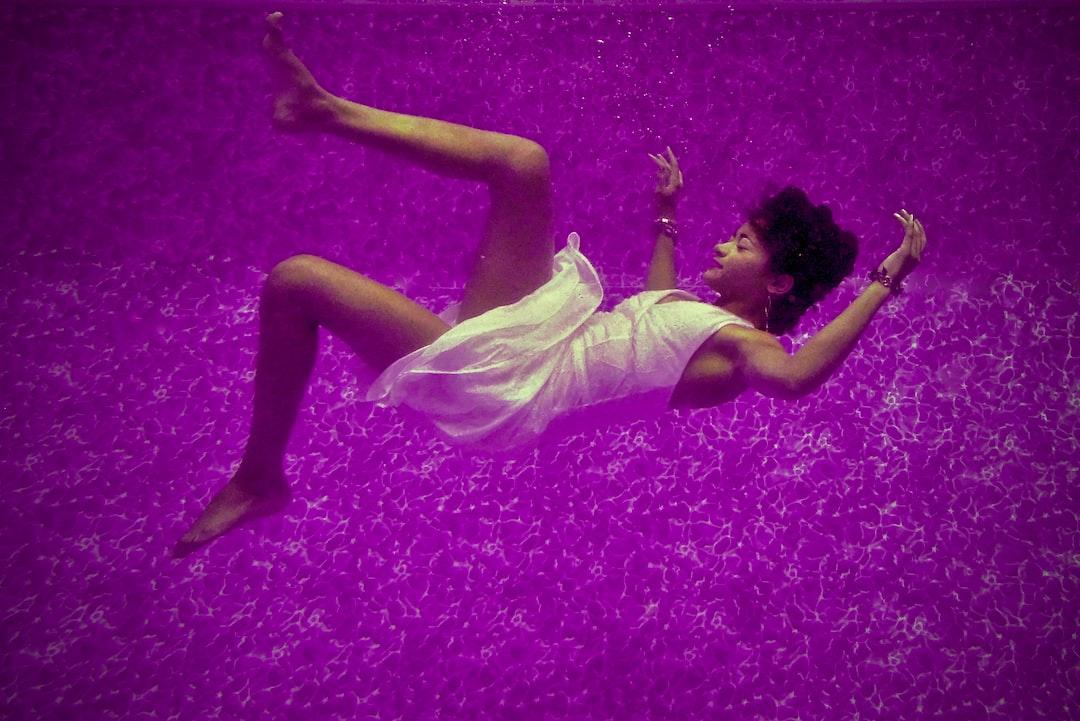 Underwater Fashion Shoot of model Savanna comfortably floating underwater in a purple pool.