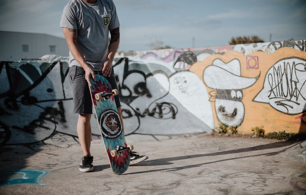 man holding teal and red skateboard