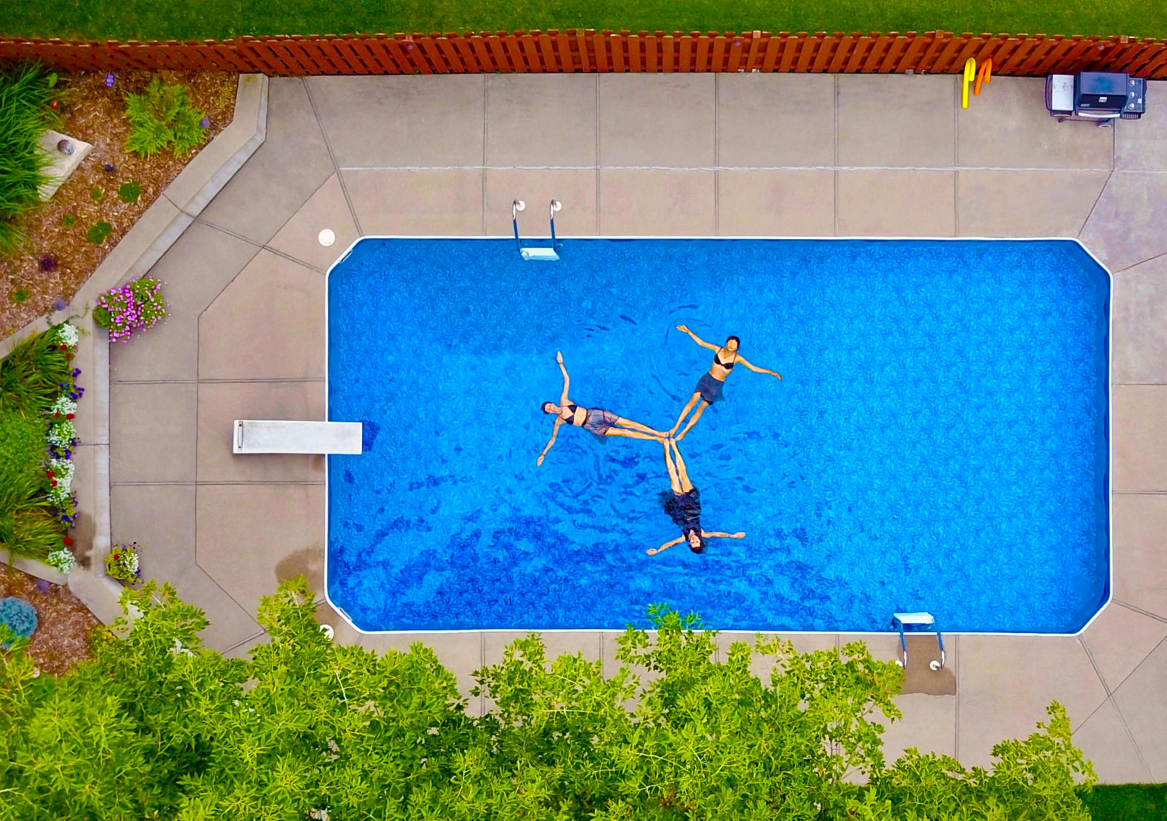 aerial photography of three women floating on pool forming propeller