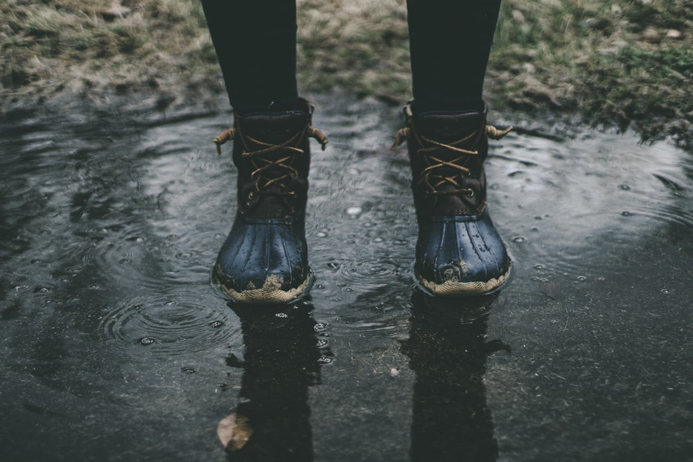 person wearing black boots standing on water