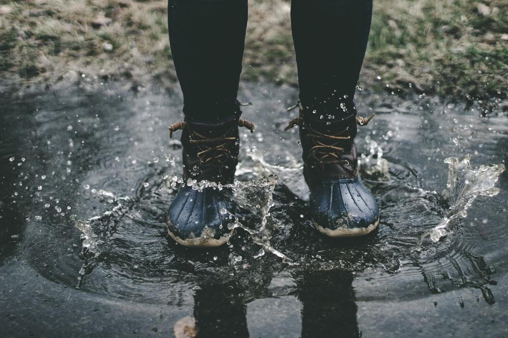 person wearing black duck boots stomping on body of water