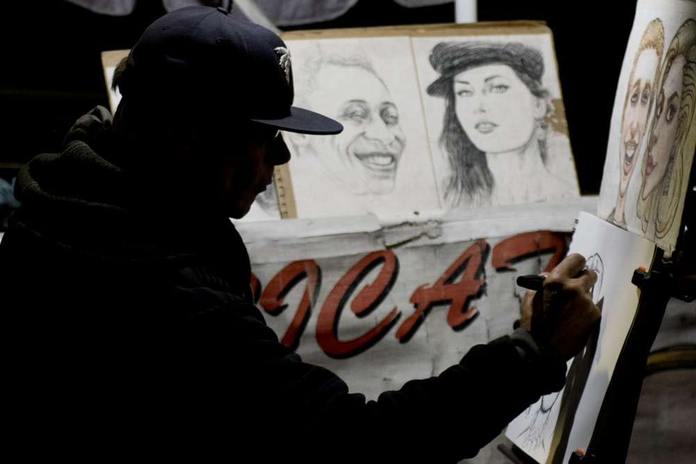 man wearing cap sitting while doing portrait sketches