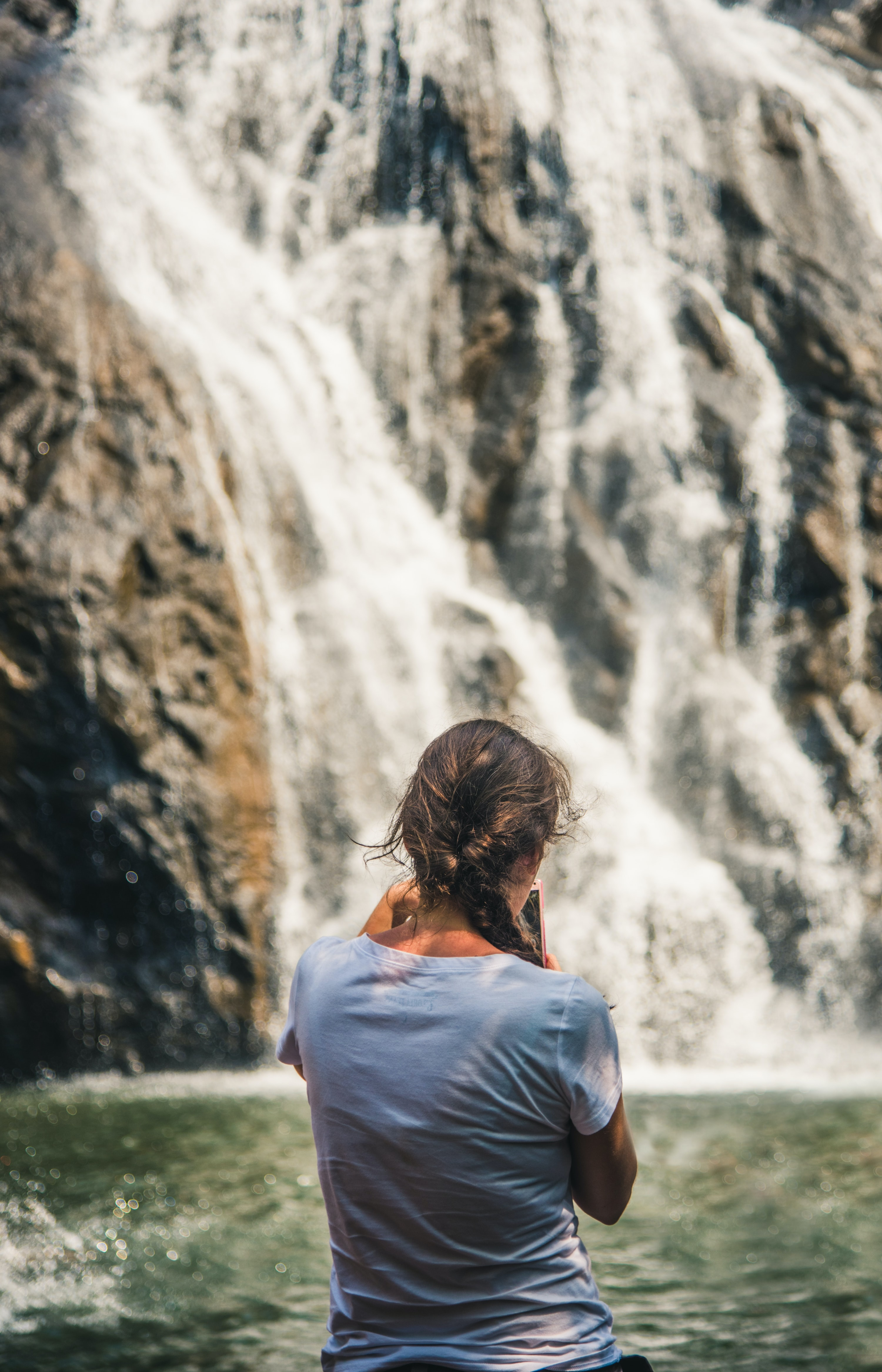 woman standing in front of waterfall