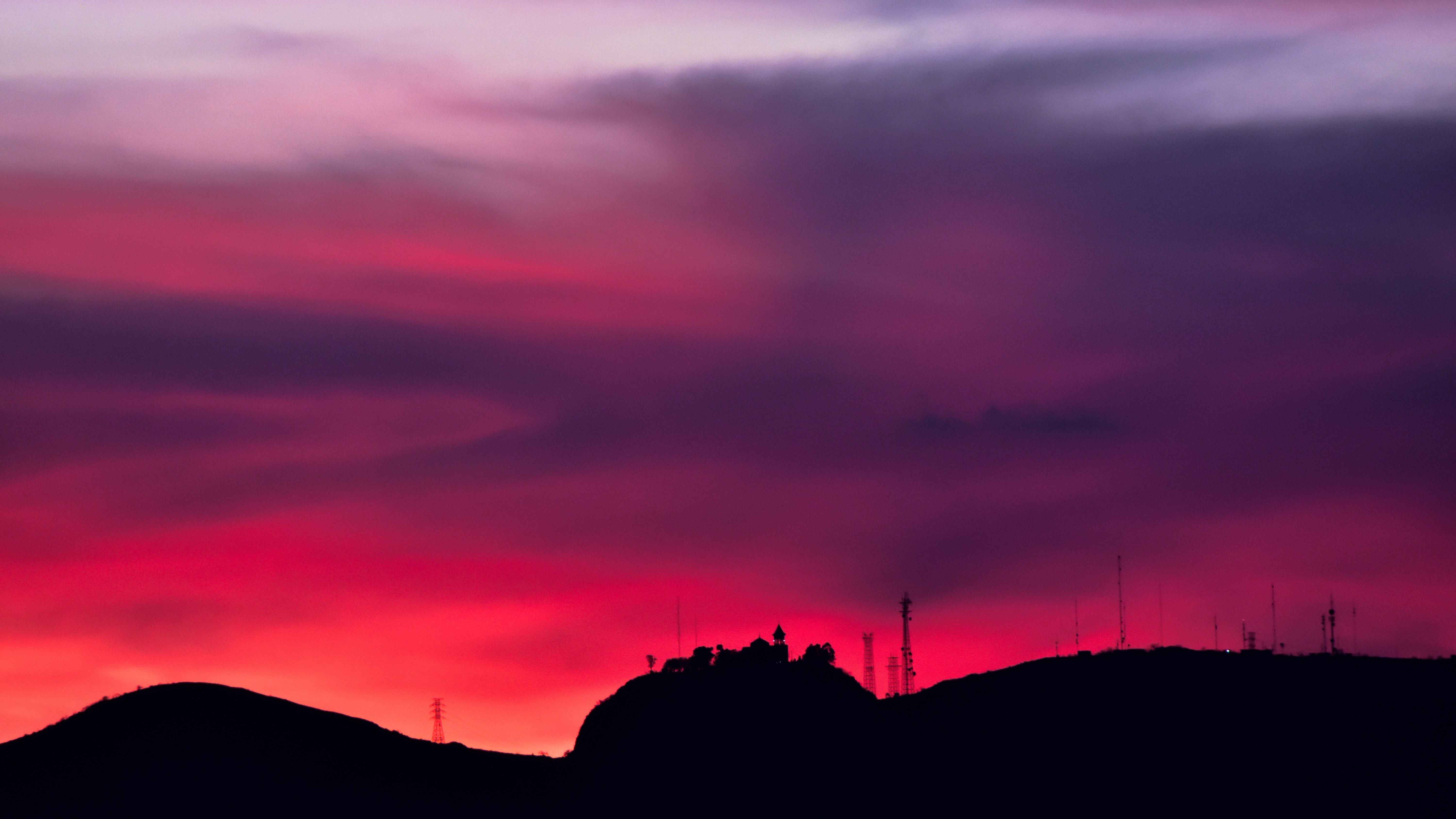 silhouette on rock under purple and pink skies