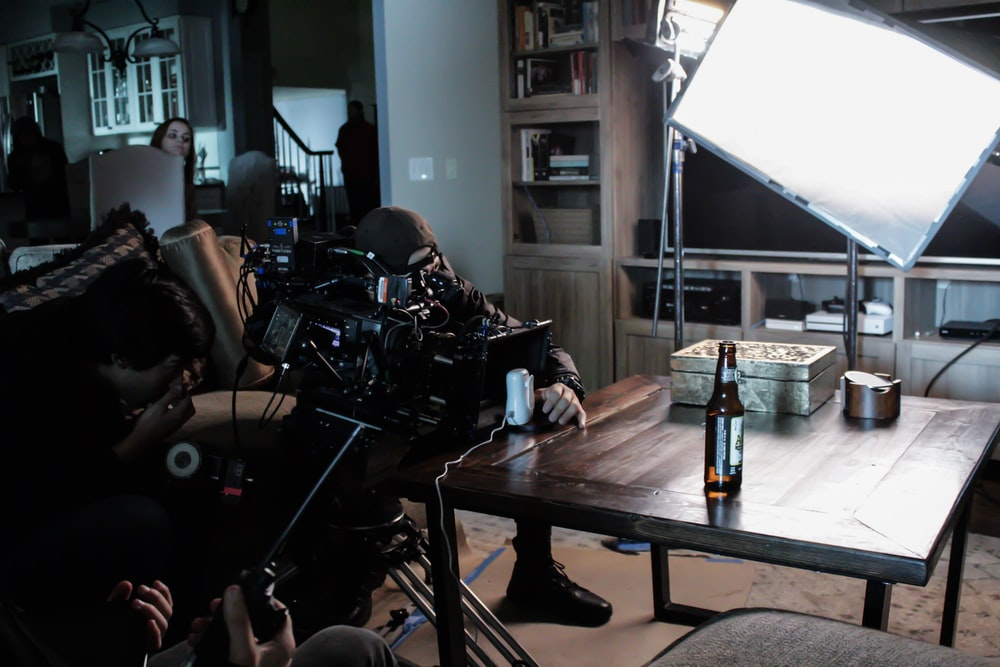 man taking a video on table near studio lamp