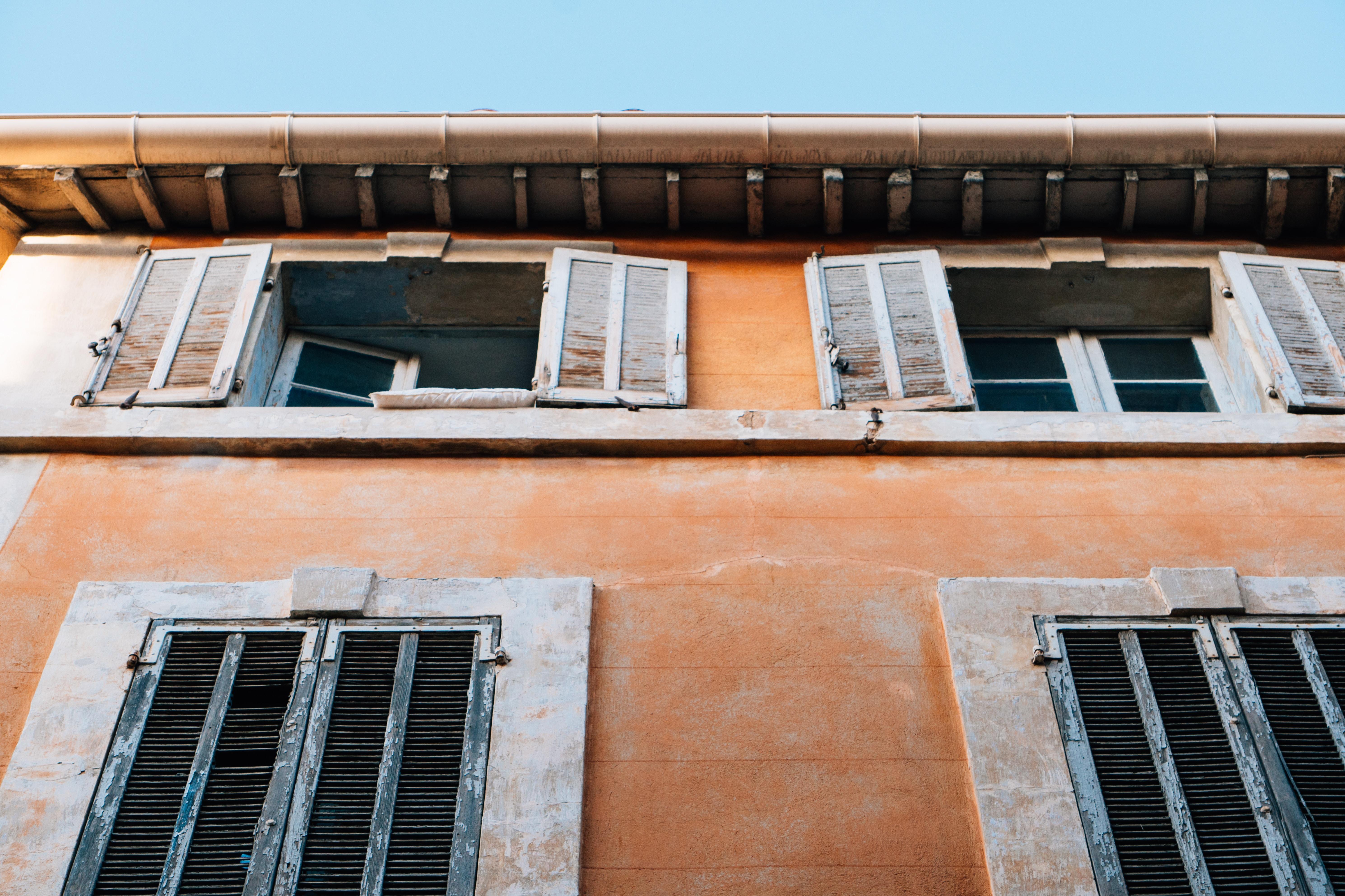 two open gray wooden louver windows