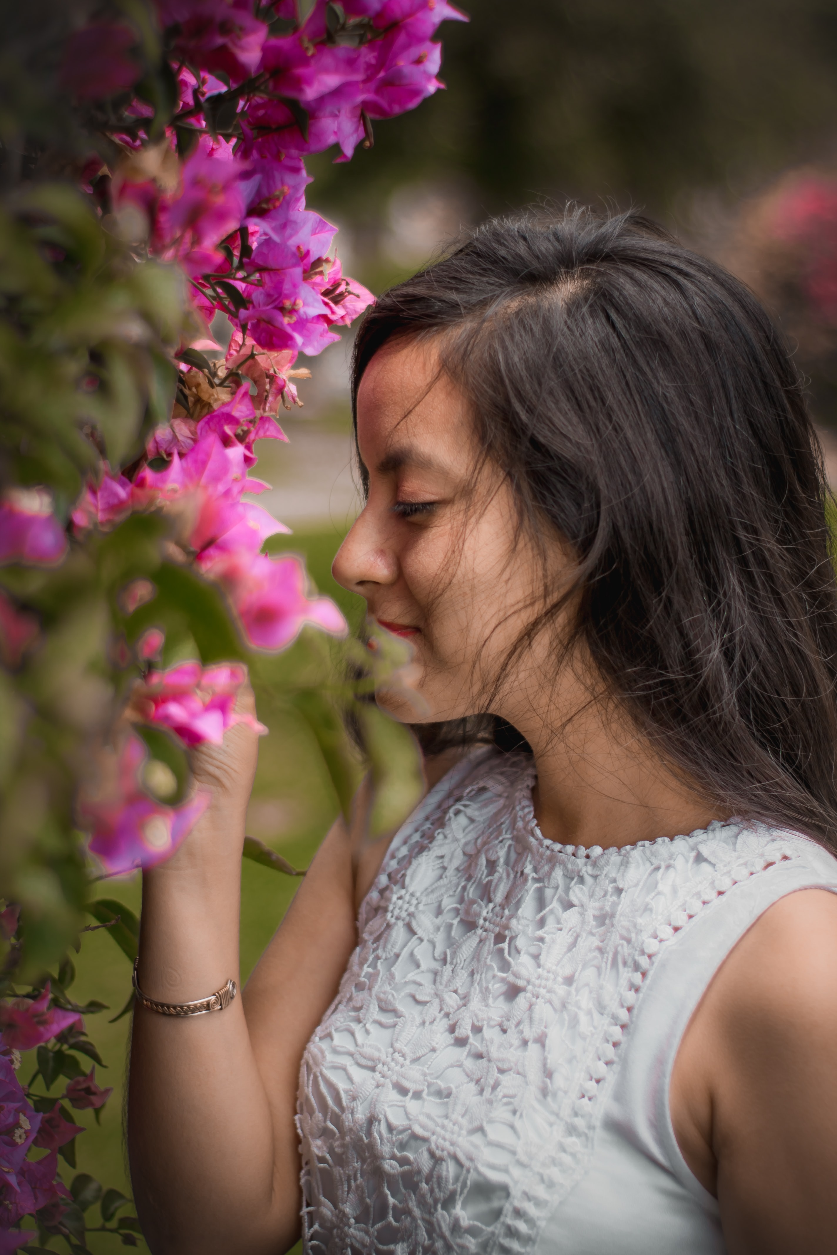 smiling woman smelling bougainvilleas in closeup shot