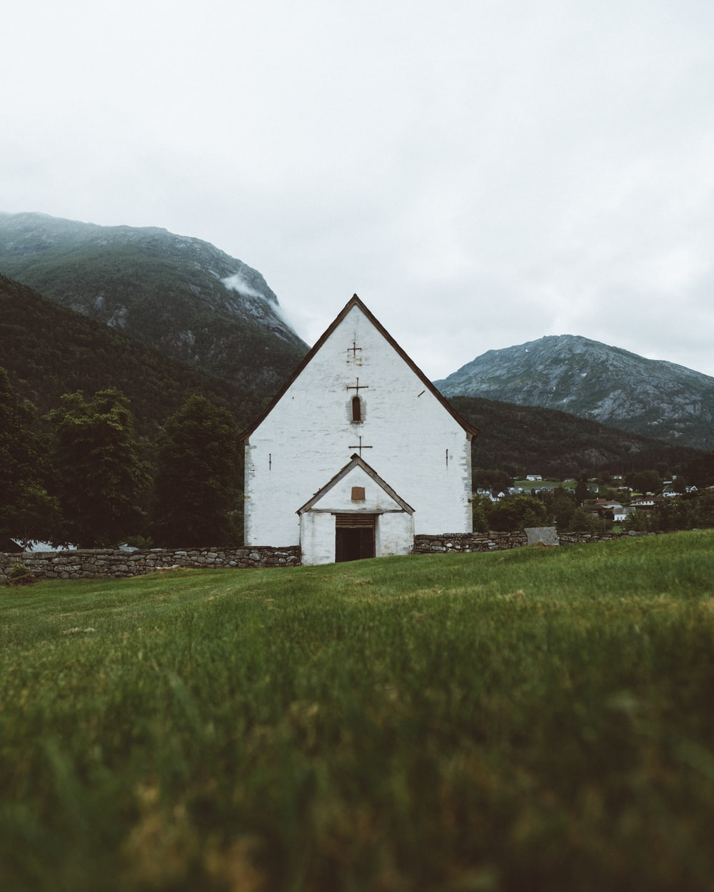 white concrete church near mountain peaks