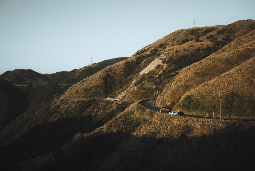 white vehicle on road near mountain at daytime