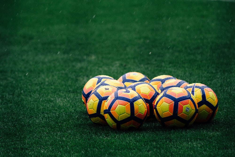 pile of yellow-orange-and-red Nike soccer balls