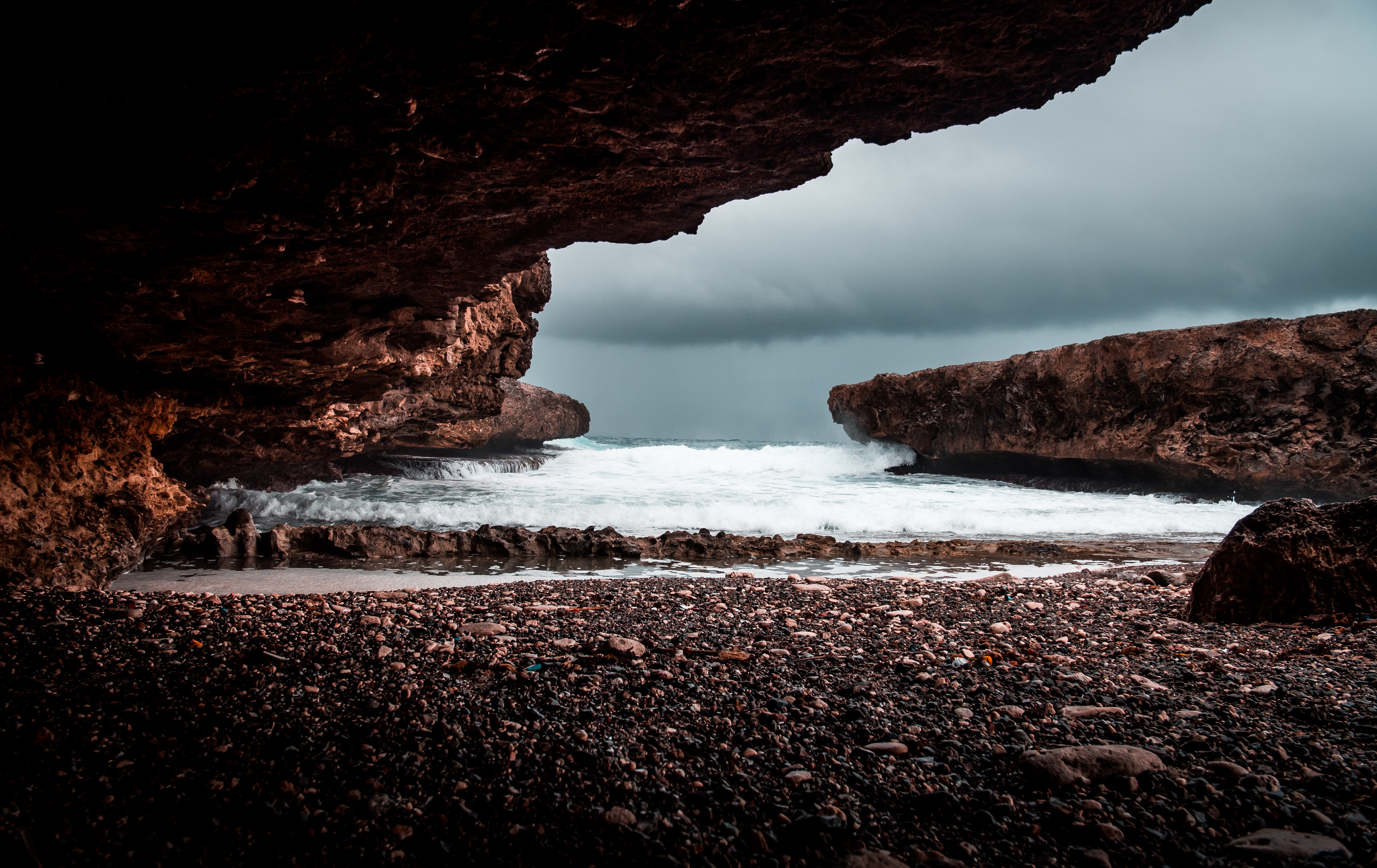 shore under rock formation during cloudy day