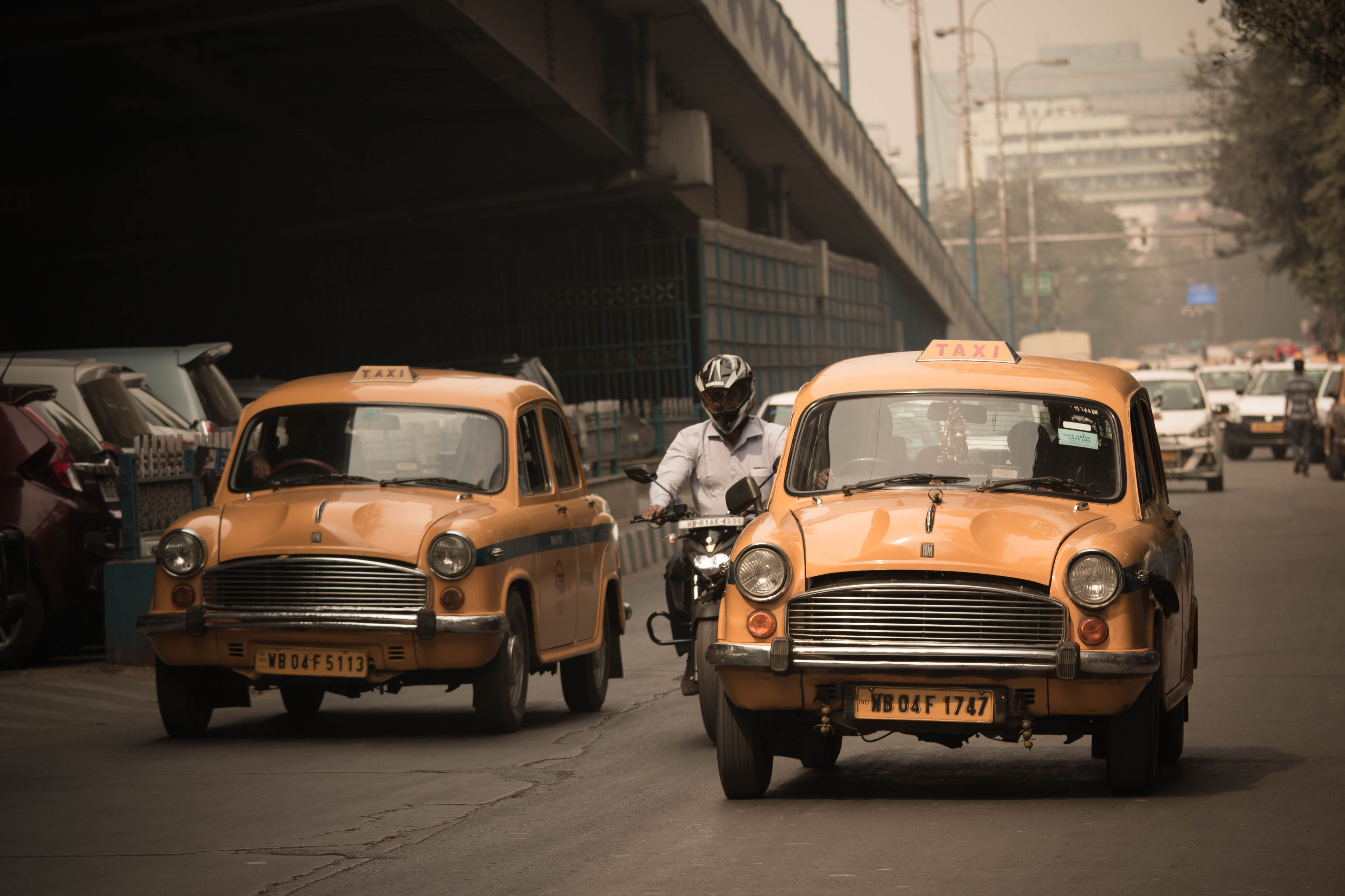 person riding motorcycle in between of two yellow taxi vehicle