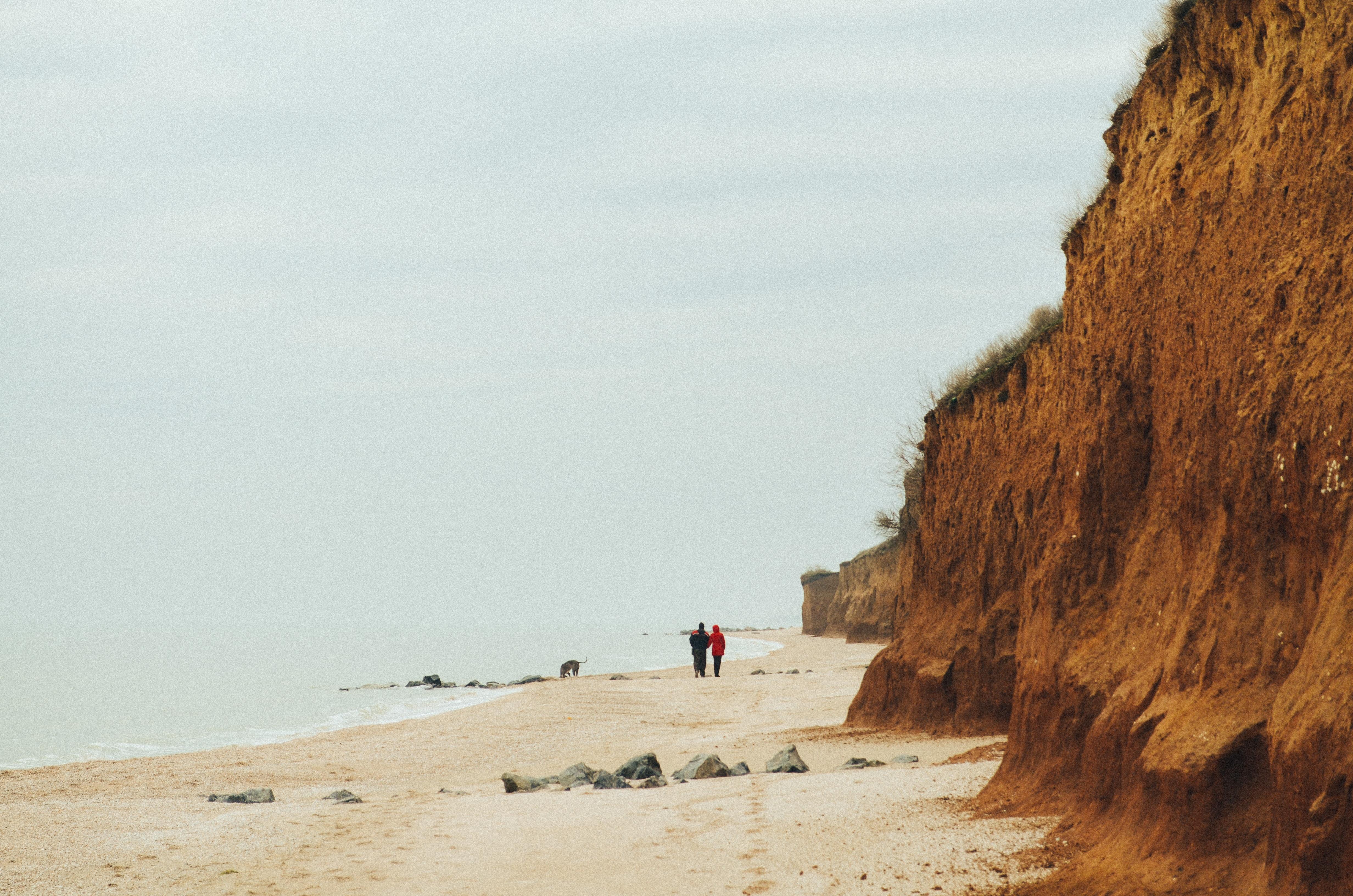 two people walking near seashore during daytime