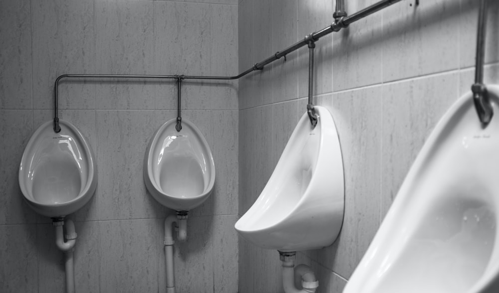 grayscale photography of four white ceramic urinal sinks