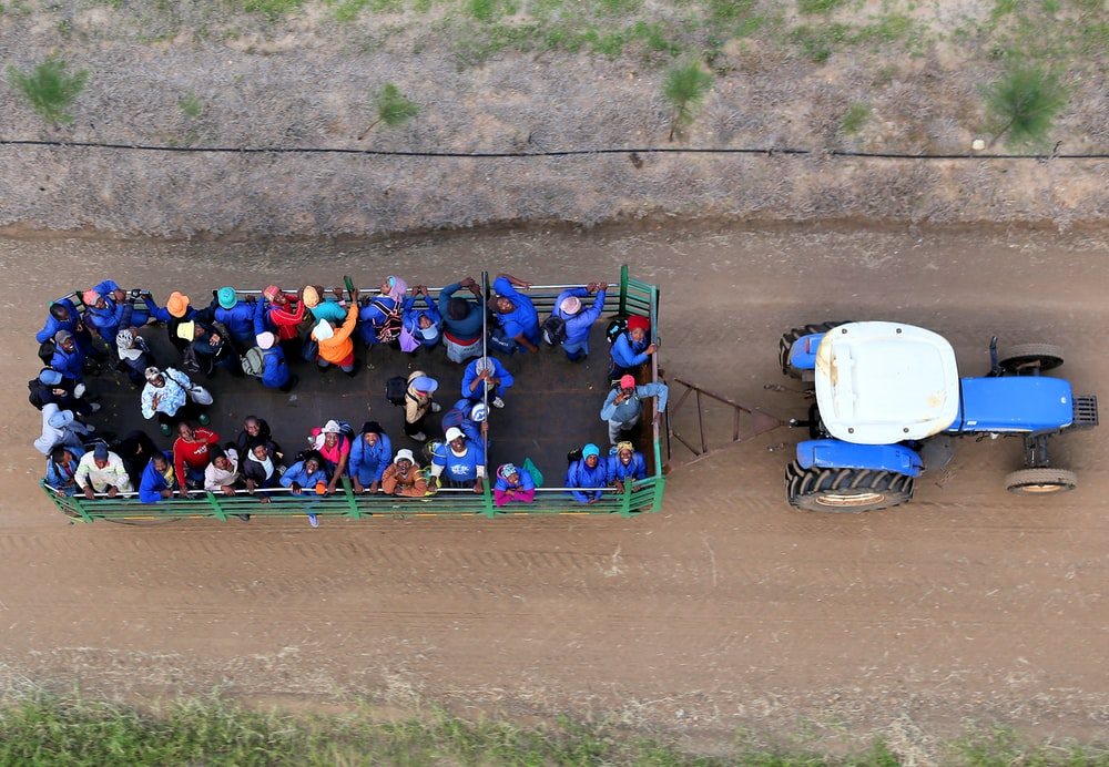 people riding on truck carried by blue tractor in top view photography