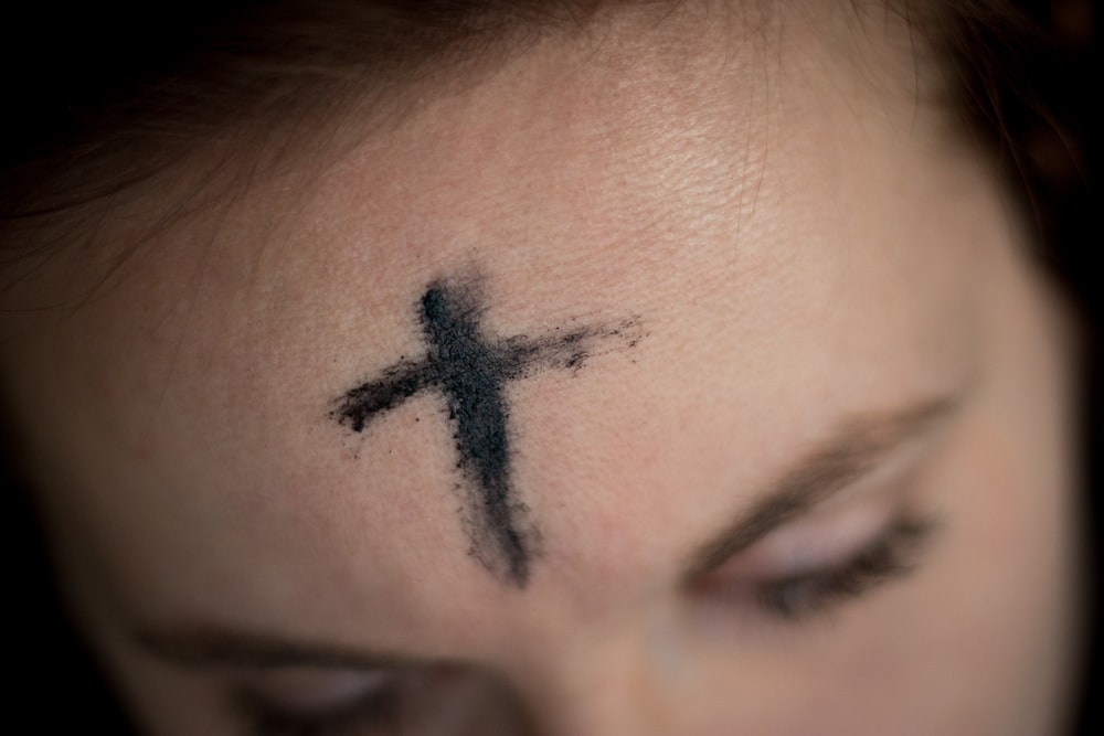 black cross on person's forehead