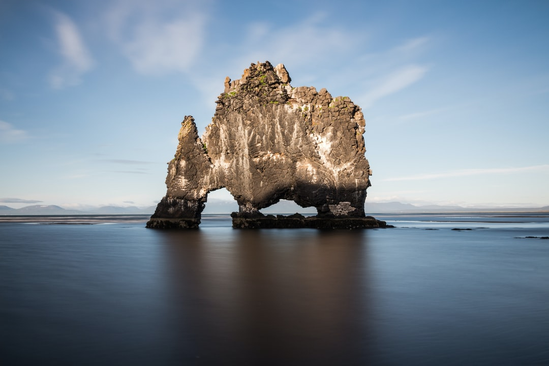 In the summer of 2014 I took a long exposure picture of this 15 m tall basalt stack, located along the eastern shore of the Vatnsnes peninsula, near Vatnsnesvegur (northern Iceland). Its name 'Hvítserkur' means 'white nightdress' because of the seabirds guano covering it. Most guides refer to its shape as a dinosaur or dragon drinking from a spring. According to the local mythology, Hvítserkur is a troll that was going to destroy a nearby monastery since he was tired of being woken up every morning by the church bells, but he underestimated the distance and was petrified when the sun came up.