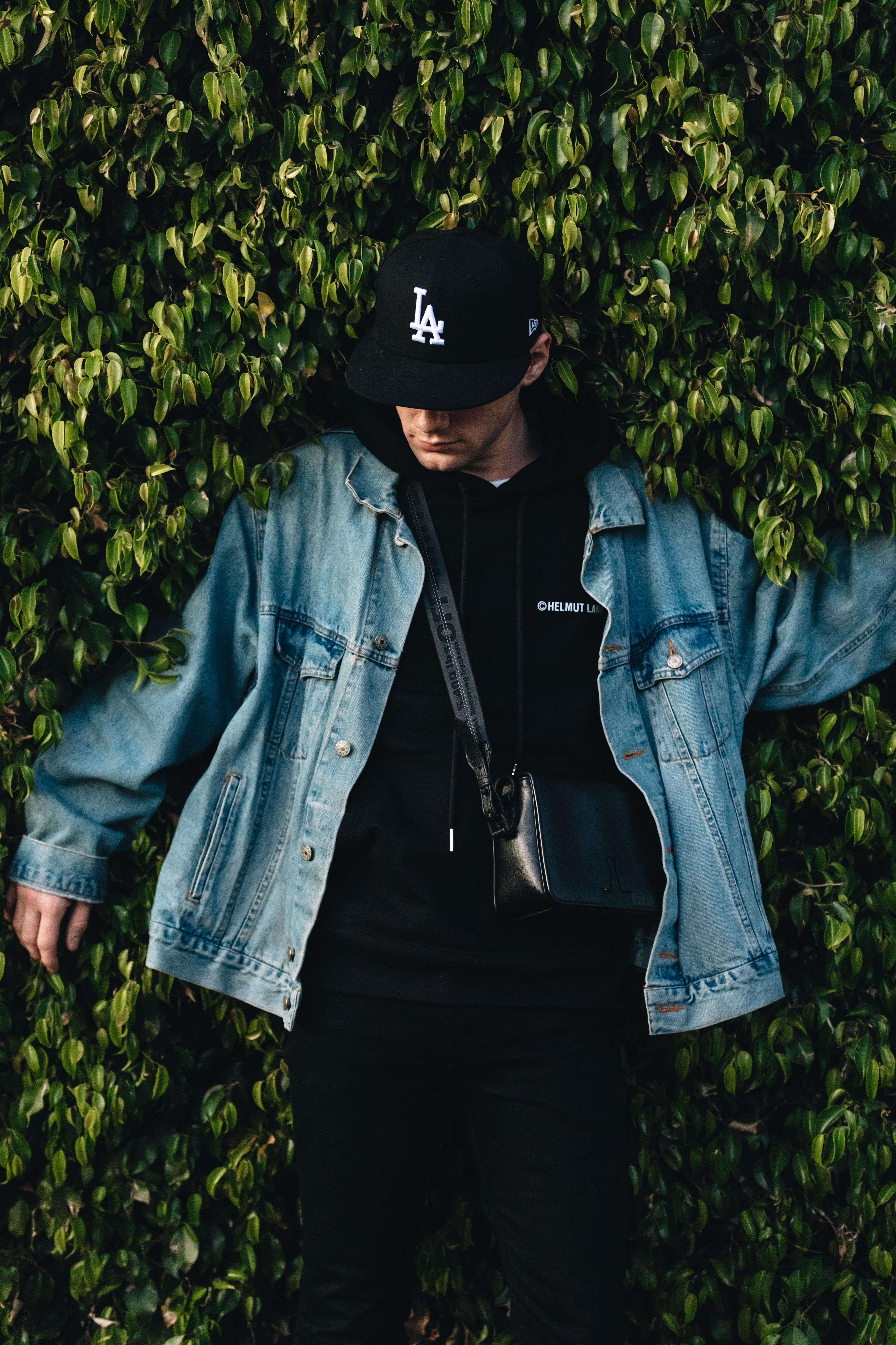 man in denim jacket beside bush