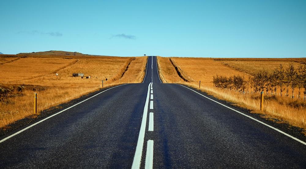 black asphalt road between brown fields during daytime