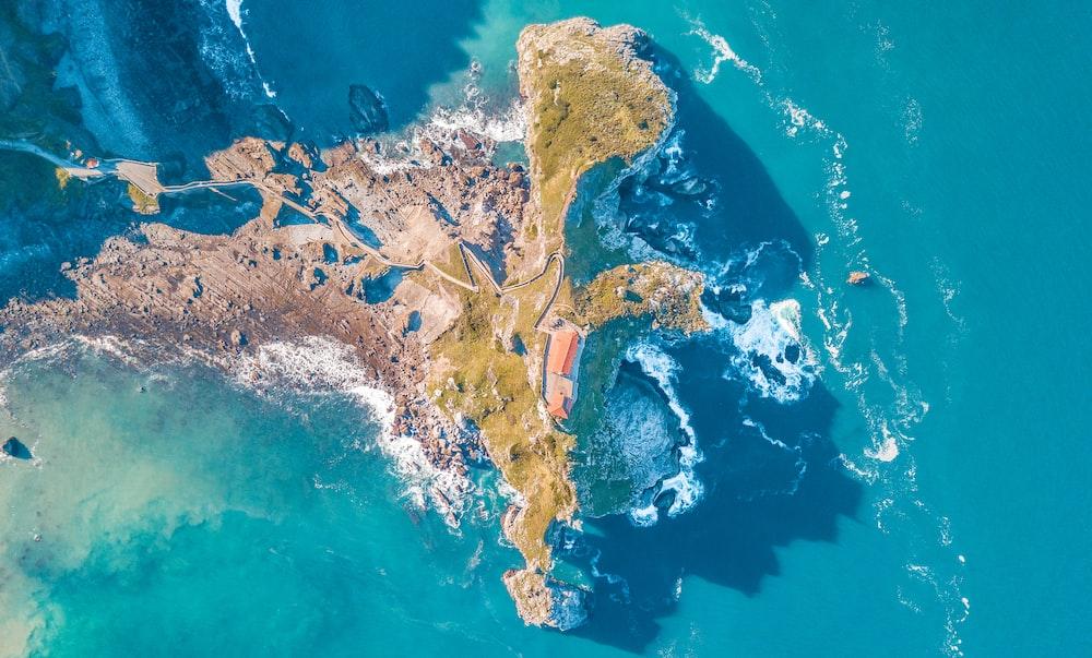 bird's eye view photo of sea waves crushing on boulders