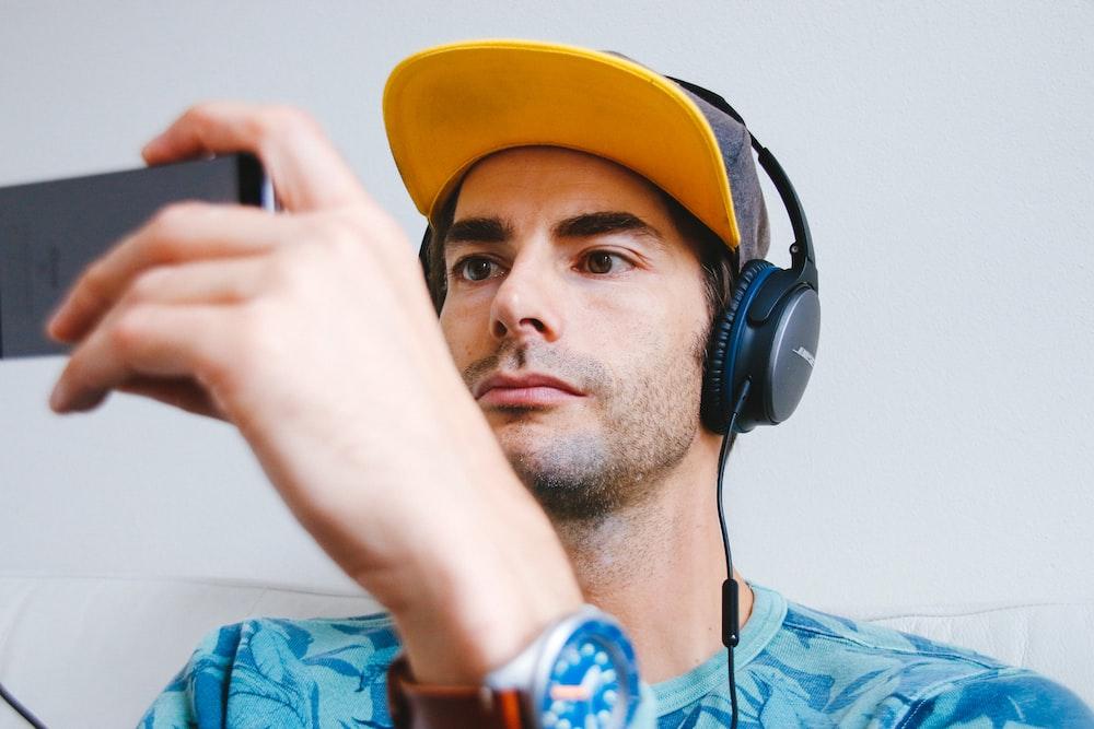 man wearing black corded headphones while holding phone