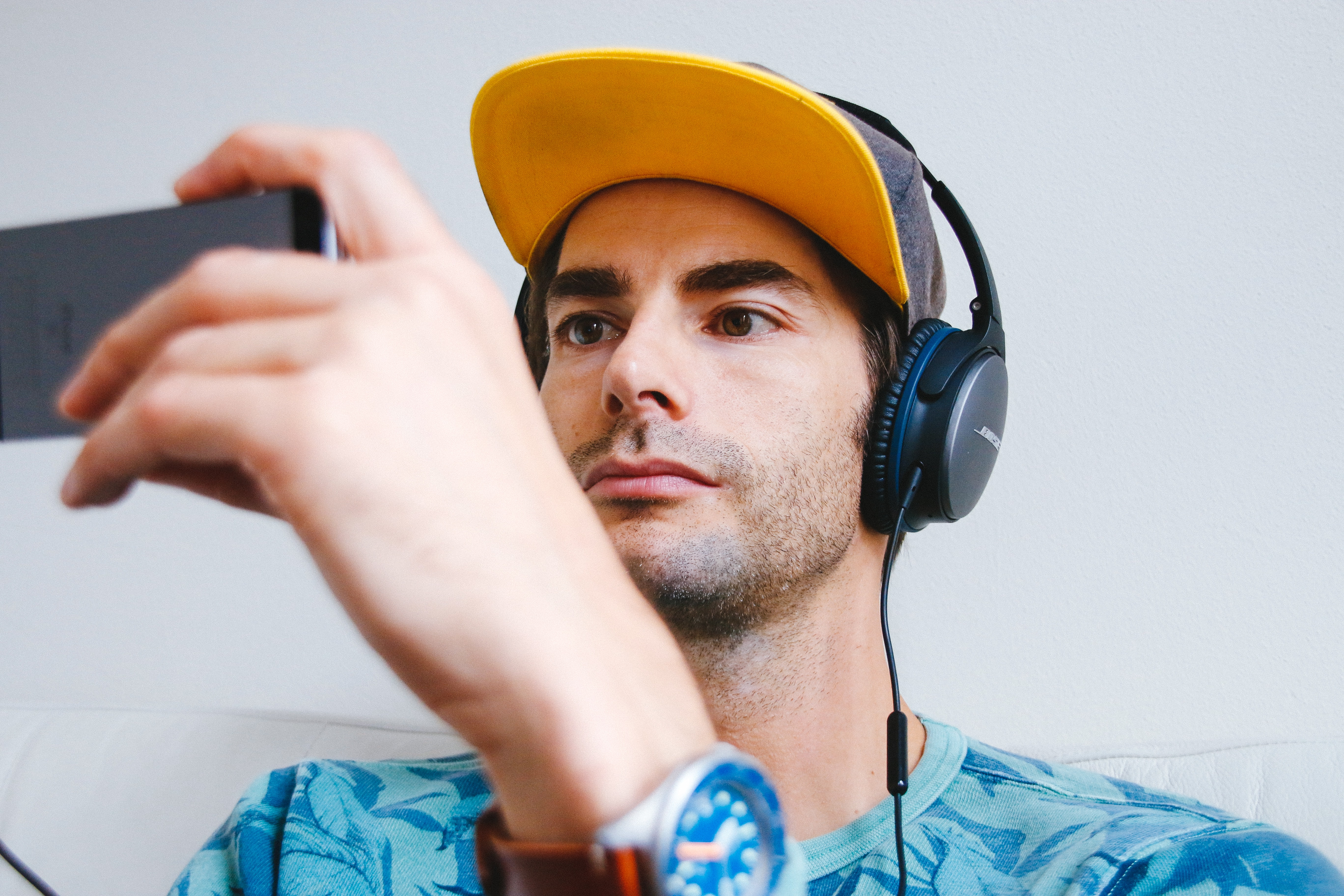 man wearing black corded headphones while holding phone