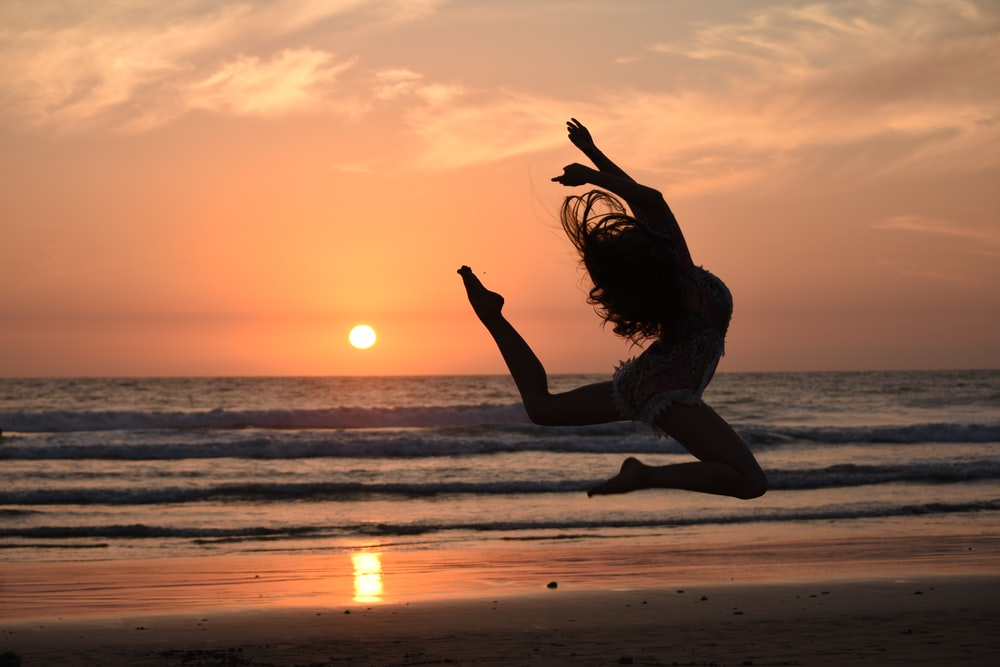 silhouette of woman jumping during golden hour