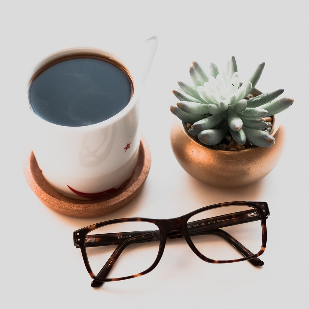 top view photo of eyeglasses beside succulent plant and coffee