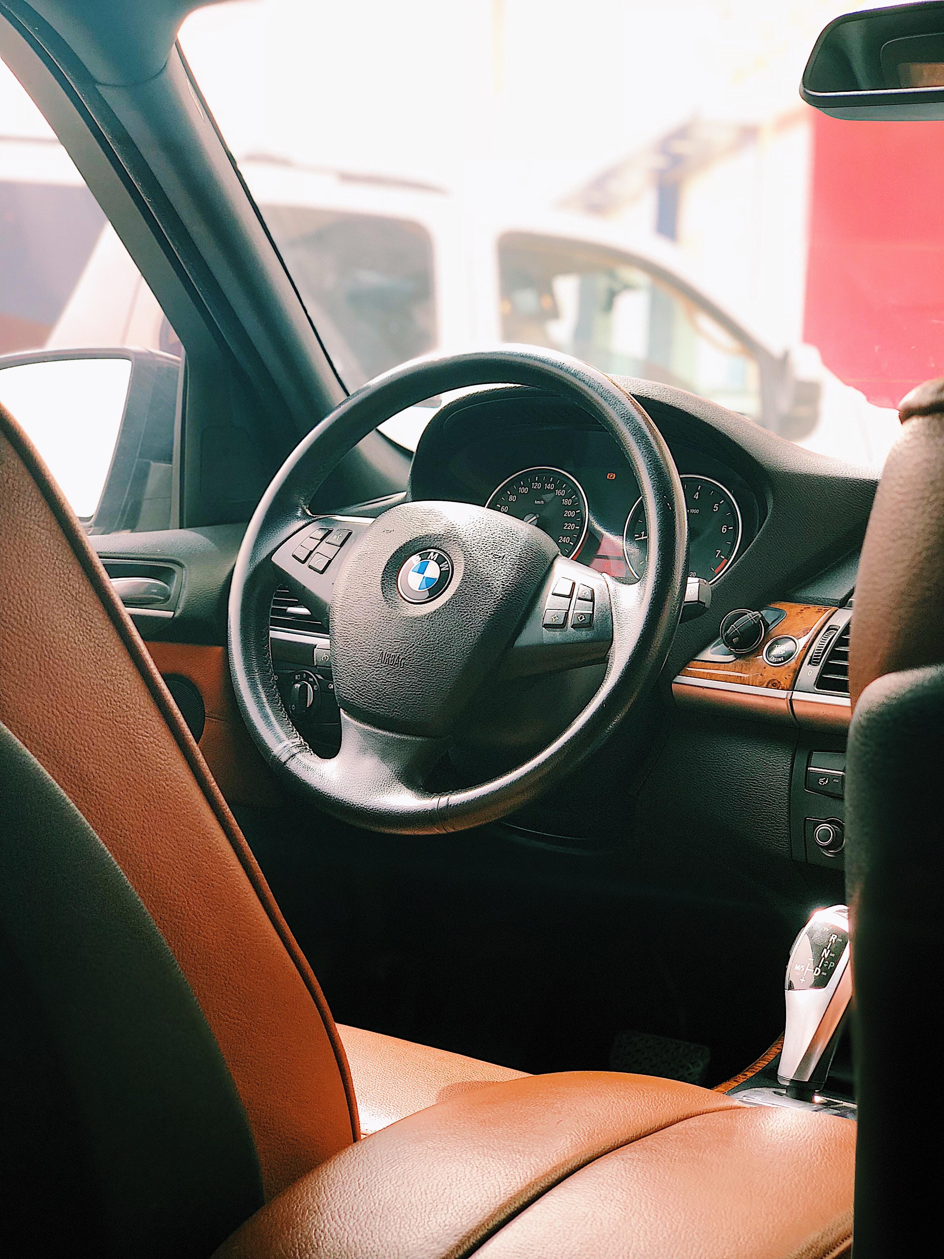 BMW vehicle interior near white van at daytime