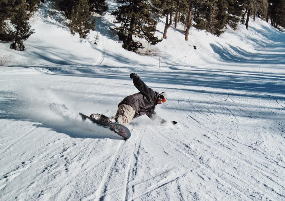 man snowboarding near green trees during daytime